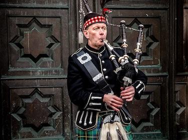 Scottish man in kilt playing bagpipes